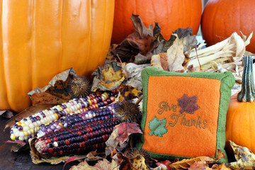 Pumpkins, leaves and Indian corn with a Give Thanks pillow.