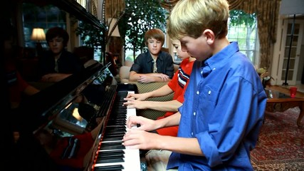 Two adolescent boys playing piano while a third looks on.
