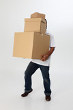 A man struggling to carry moving boxes. poster