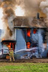 Fireman hosing down a burning house