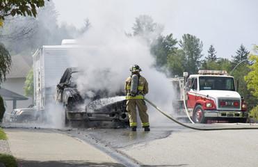 Fireman extinguishing burning vehicle