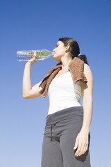 Young sexy woman drinking water after exercise