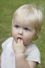 portrait of  blond serious baby girl. Her fingers in mouth