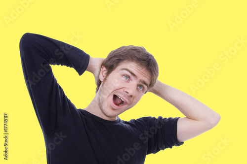 Yawning casual man, isolated on Yellow background