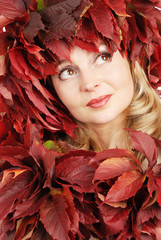 Portrait of the young beautiful woman with autumn leaves
