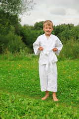 karate boy stands on lawn