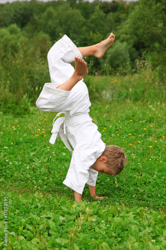 karate boy does handstand on lawn