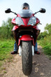 motorcyclist standing on country road, closeup, front view