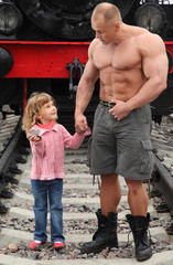 strong shirtless man stands on railroad with little girl