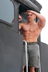 strong shirtless man keeps watch on locomotive