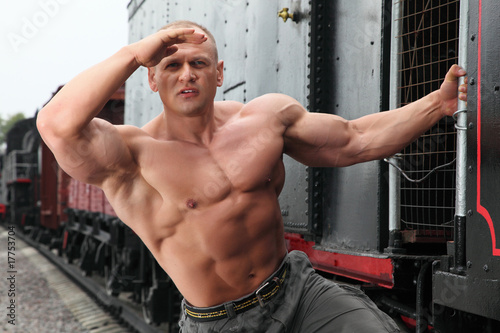 strong shirtless man keeps watch on locomotive