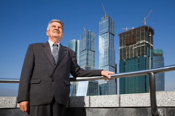 smiling senior man in suit near skyscrapers construction