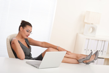 Female manager working with legs up