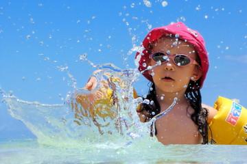 Fillette jouant dans l'eau azur d'un lagon.