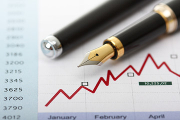 Fountain pen on business charts and graph
