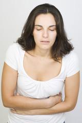 Junge hübsche Frau mit Bauchschmerzen