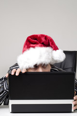 Man hiding behind laptop with Christmas hat