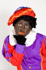 girl dressed up as zwarte piet blowing a handkiss