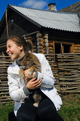 Young beautiful smiling girl pets a puppy