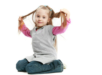 little beautiful girl sit and touch her hair on white