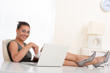 Attractive businesswoman having coffee and feet on table