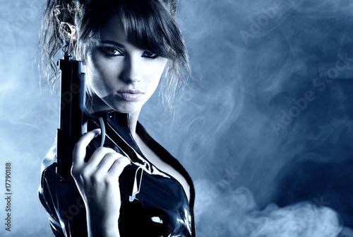 Belle fille sexy holding gun. fumée fond Poster