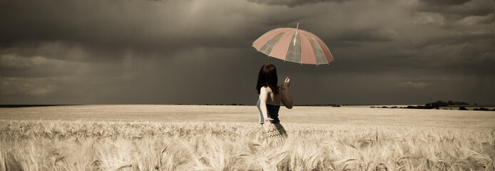 Girl with umbrella at field in retro style panoramic.