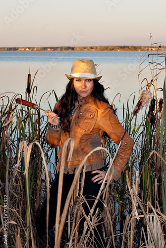 Young woman at the lake in hat