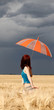 Girl with umbrella at field