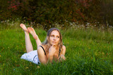 Beautiful young woman on the grass.