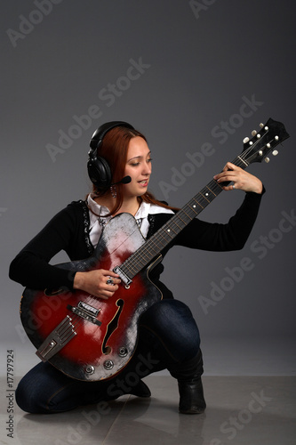 Girl sitting with bass guitar and play music