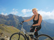 happy young woman on mountains with bike