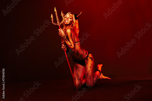Beautiful devil with trident and Halloween accessories