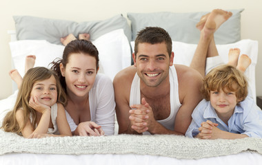 Portrait of happy family lying in bed