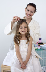 Mother doing her daughter's hair