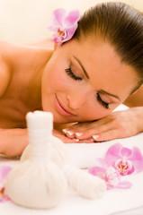 Hübsche Frau bekommt Kräuterstempel Massage