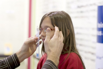 enfant qui essaye ses lunettes chez l'opticien