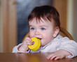 Baby  gnawing a yellow toy