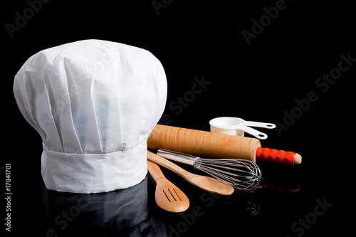 A chef's toque with cooking utensils