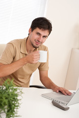 Young modern businessman with cup of coffee