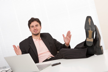 Young businessman gesturing at office