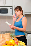woman checking bill and talking on phone in the kitchen