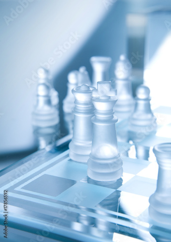 White transparent pieces of chess on chess board made of glass.