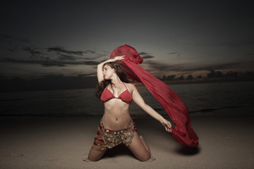 Beautiful belly dancer on the beach