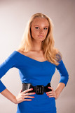 serious young blonde girl in blue dress isolated on gray