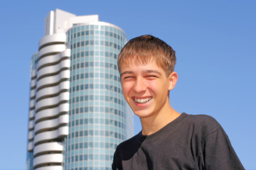 The cheerful teenager on the skyscraper background
