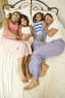 Young Family Relaxing In Bedroom