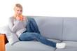 Attraktive Frau genießt einen Kaffee auf der Couch