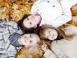 Three girls lying in leaves