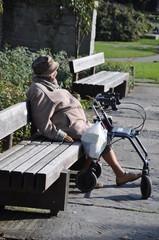 Ältere Dame auf der Parkbank